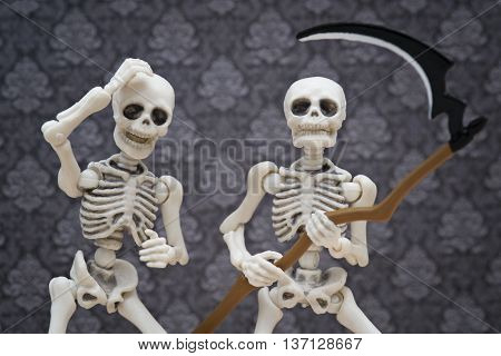 A skeletons holding a scythe and his friend beside him