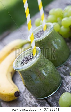 Healthy detox green smoothie with spinach grape and banana on old wooden table