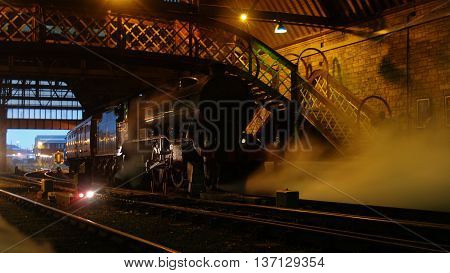 Steam locomotive waits in the evening light.
