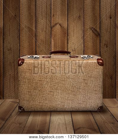 Vintage suitcase on rough wooden plank background