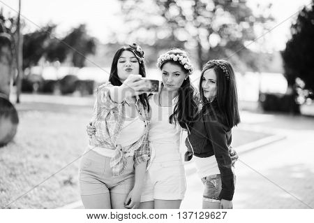 Three Girls In Short Shorts And Wreaths On Heads Make Selfie