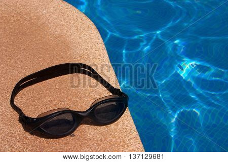 Dive goggles at the border of a swimming pool