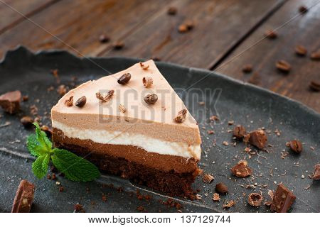 Layered suffle cake on black plate, decorated with chocolate chips and coffee beans on wooden background