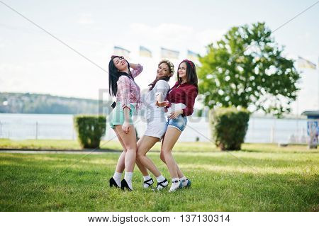 Three Happy Girls In Short Shorts And Wreaths On Heads Dancing And Having Fun On Green Grass At Bach