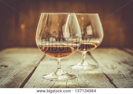 Cognac in glasses on rustic backgrpund, copy space, toned