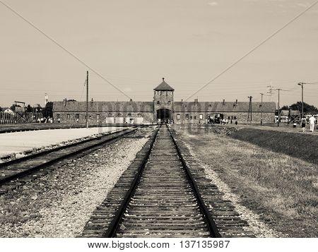 Main gate and railroad in Brzezinka, or Birkenau, nazi extermination camp, Oswiecim, or Auschwitz, Poland. Sepia style image.