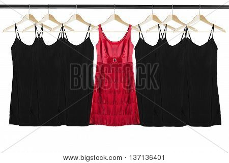 Red silk dress among black identical dresses on clothes racks isolated over white