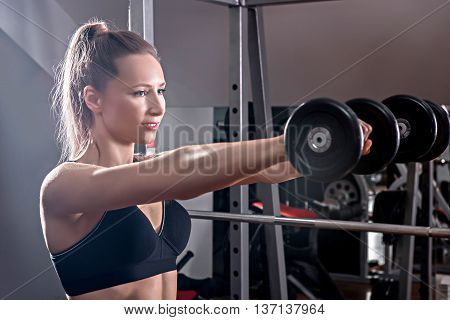 Strong woman weightlifting at the gym. Woman working out with dumbbells at a gym. Dumbbell bicep curl by a fitness girl. In good condition