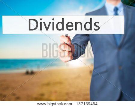Dividends - Businessman Hand Holding Sign
