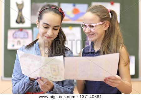 Two schoolgirls consider drawings on drawing lesson in classroom and smiling