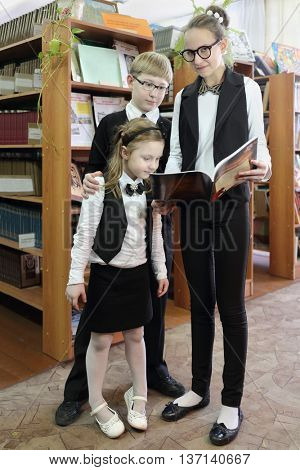 Three students, two girls and boy looking in book that holds eldest girl