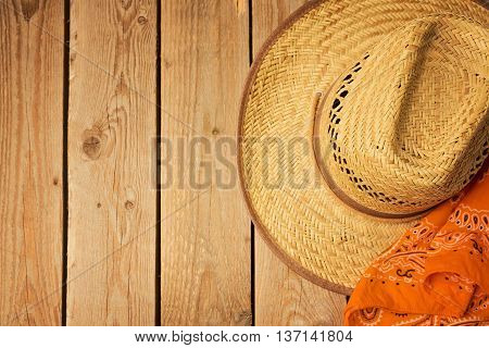 Cowboy hat on wooden vintage table with bandanna. View from above