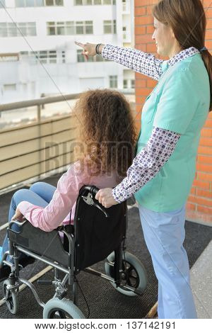 Nurse and patient in wheelchair on balcony in hospital breathing fresh air, nurse held his hand in front of what is showing