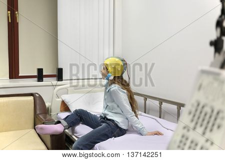 patient girl on procedure of removing of electroencephalogram, sitting on bed looking out window closed