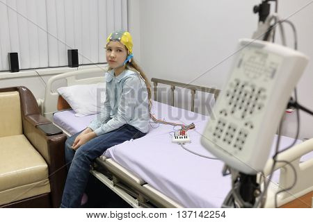 patient girl on procedure of recording of electroencephalogram, sitting on bed looking at camera