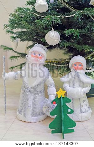 toy statuettes Snow Maiden, father frost and  small christmas tree under new year tree, close-up