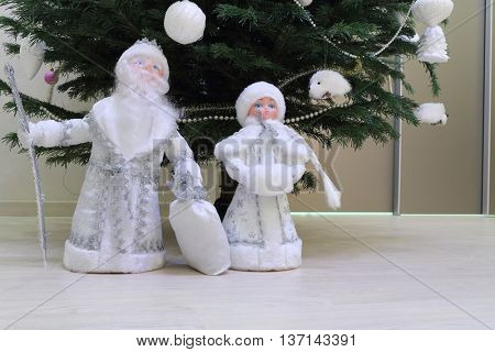 toy statuettes Snow Maiden and father frost under Christmas tree, close-up