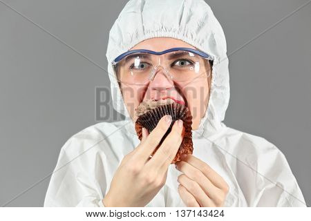 Half-length portrait of woman biting piece of tasty chocolate cake and looking at us, on gray background