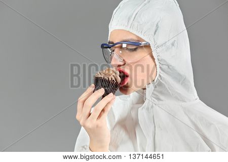 Half-length portrait of woman biting piece of tasty chocolate cake and looking on cake, on gray background