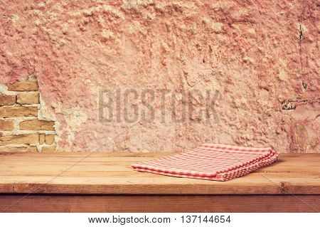 Empty wooden deck table with checked napkin over vintage wall background