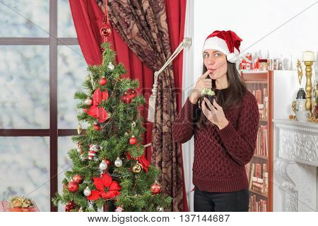 Half-length portrait of woman in burgundy sweater holding piece of tasty chocolate cake and licking finger. Christmas interior with tree on background