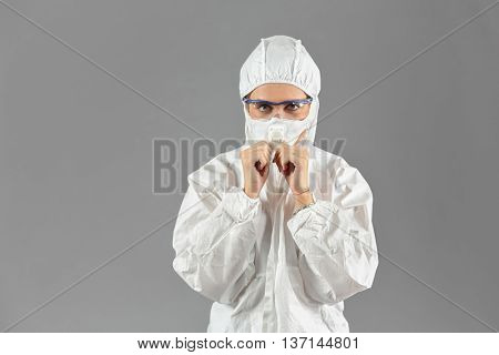 Half-growth portrait of woman in white protective suit of synthetic paper and respiritory half mask, looking at us, on gray backgroun