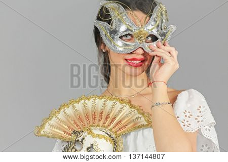half-length portrait of young woman in carnival mask, holding another mask in hand, look at us, close-up