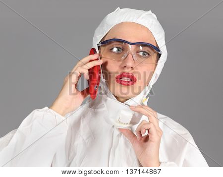 headshot of woman in white protective suit of synthetic paper, glasses and respiritory half mask, talking on phone, disquieted, on gray background