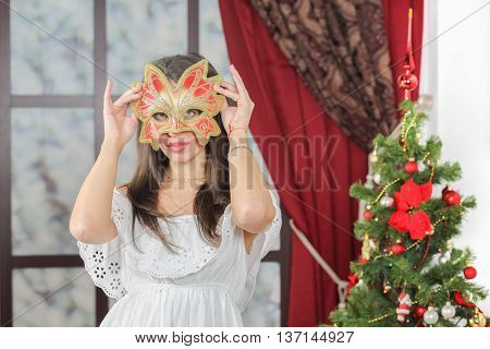 Half-length portrait of young woman in carnival mask standing near christmas three, look at us. Christmas interior studio