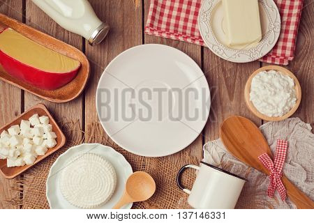 Milk and cheese around empty plate on wooden background. View from above. Flat lay.