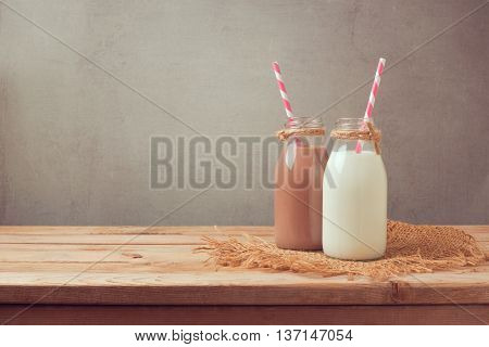Milk bottle and chocolate milk bottle on wooden table. Healthy eating concept