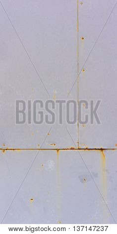 part of the gray rusty scratched metal gate covered with dark orange stains and rusty strips it is visually divided into three parts,