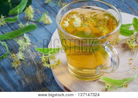 Cup with linden tea and flowers on wooden table. concept of treatment cold and flu
