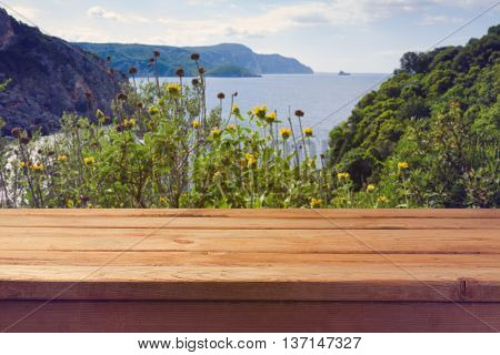Summer holiday background. Empty wooden table over beautiful sea landscape
