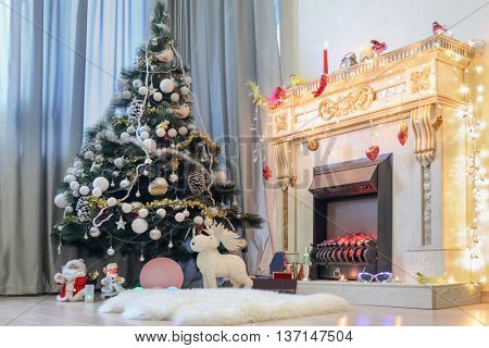 Fireplace and perfect Christmas tree with gifts underneath in living room