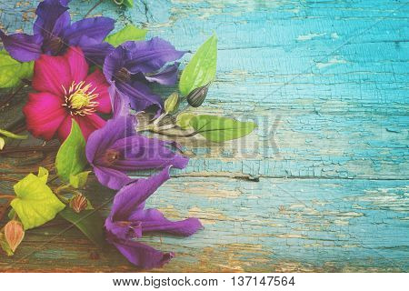 Background with blue Clematis flowers on cracked paint wooden planks. Top view with copy space, tinted