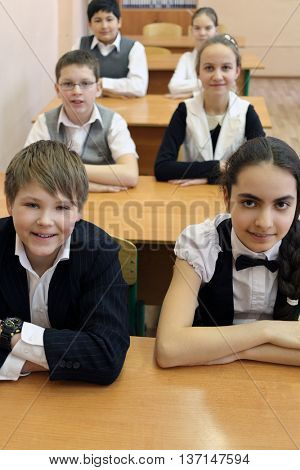 three boys and three girls in classroom sitting at desk in classroom, smile and look at camera, focus on boy and girl in foreground