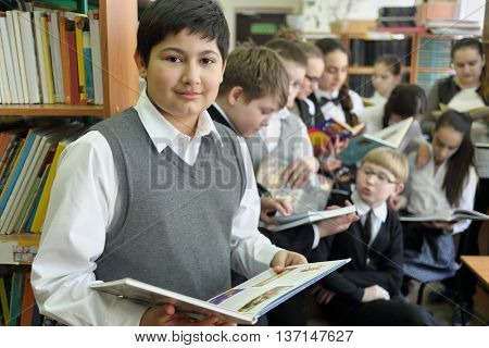 Ten students in school library reading books on background of shelves with books, one in foreground looking into camera, focus on boy left