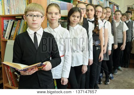 Eleven students in school library are to each other, boy in foreground holding book in his hands, everyone is looking at camera, focus on boy left
