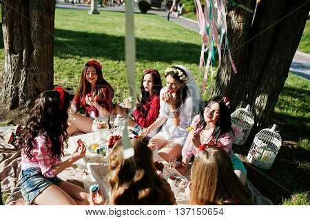 Seven Happy And Sexy Girls Sitting At Picnic Table And Eating Strawberries On Bachelorette Party