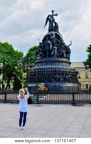 VELIKY NOVGOROD RUSSIA -JUNE 11 2016. Unidentified tourist girl taking the shot of the monument Millennium of Russia - famous bronze monument dedicated to Russia's 1000 year anniversary