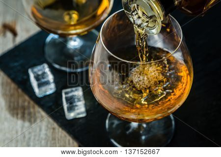 Pouring cognac in a glass, rustic background