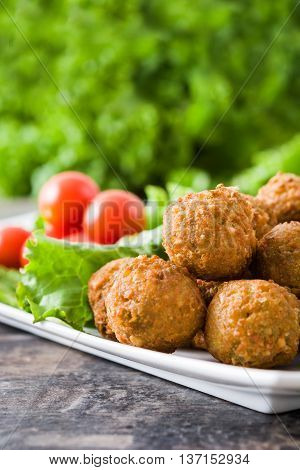 Vegetarian falafels and vegetables on a rustic wood