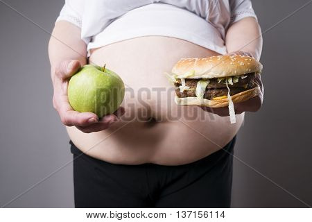 Fat women suffer from obesity with big hamburger and apple in hands junk food concept on a gray background