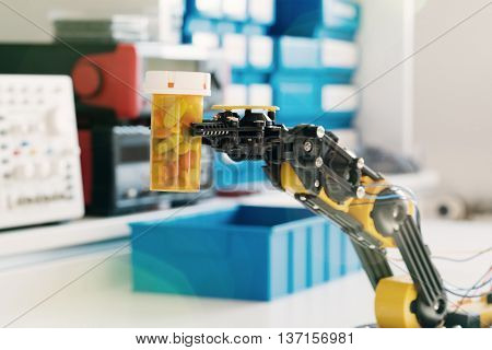 Plastic model of industrial robotics arm Robot manipulator and vial with pills