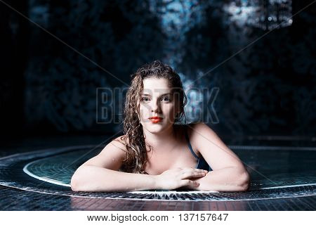 Beautiful young blonde caucasian woman in bikini with waterproof makeup relaxing in hot pool or jacuzzi at spa center water treatment and body care concept