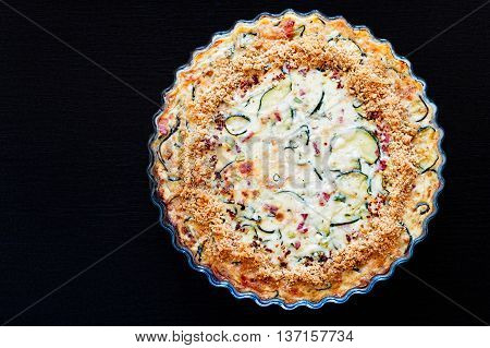 Top view of homemade crustless zucchini quiche baked in a glass fluted dish on a black wooden board