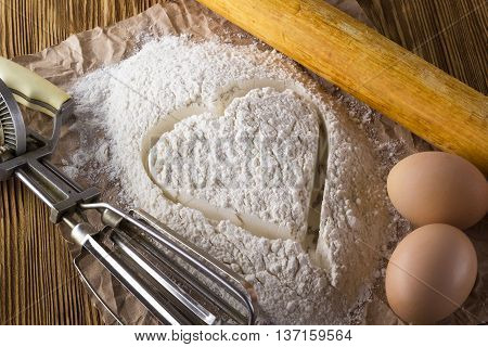 Eggs, a Hand Mixer and a Bowl of Flour on a Wooden Table