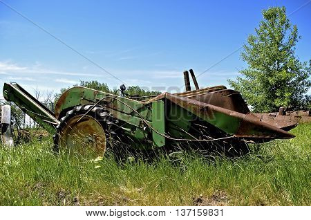 An old mounted green corn picker is mounted on the front end of a a tractor