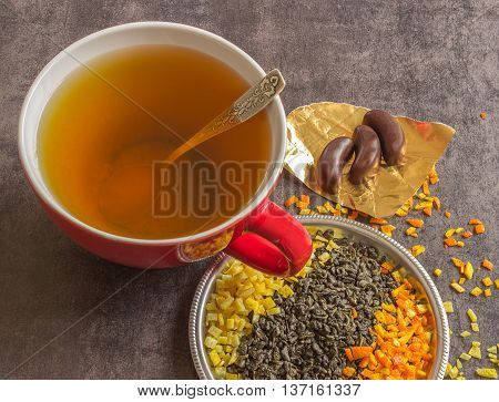 Large cup of hot green tea on a dark background. Scented dry tea with orange peel and lemon.